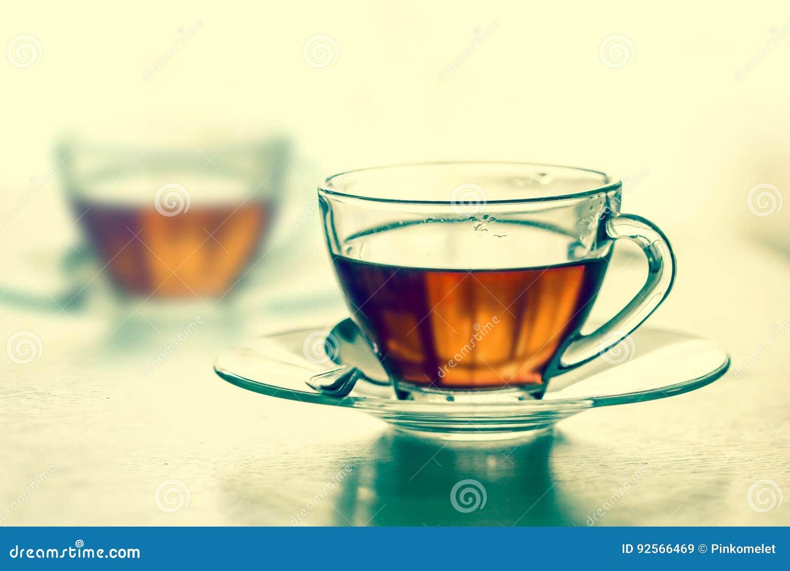 Chiuda su caldo la tazza di tè nero sulla tavola di legno in ro vivente
