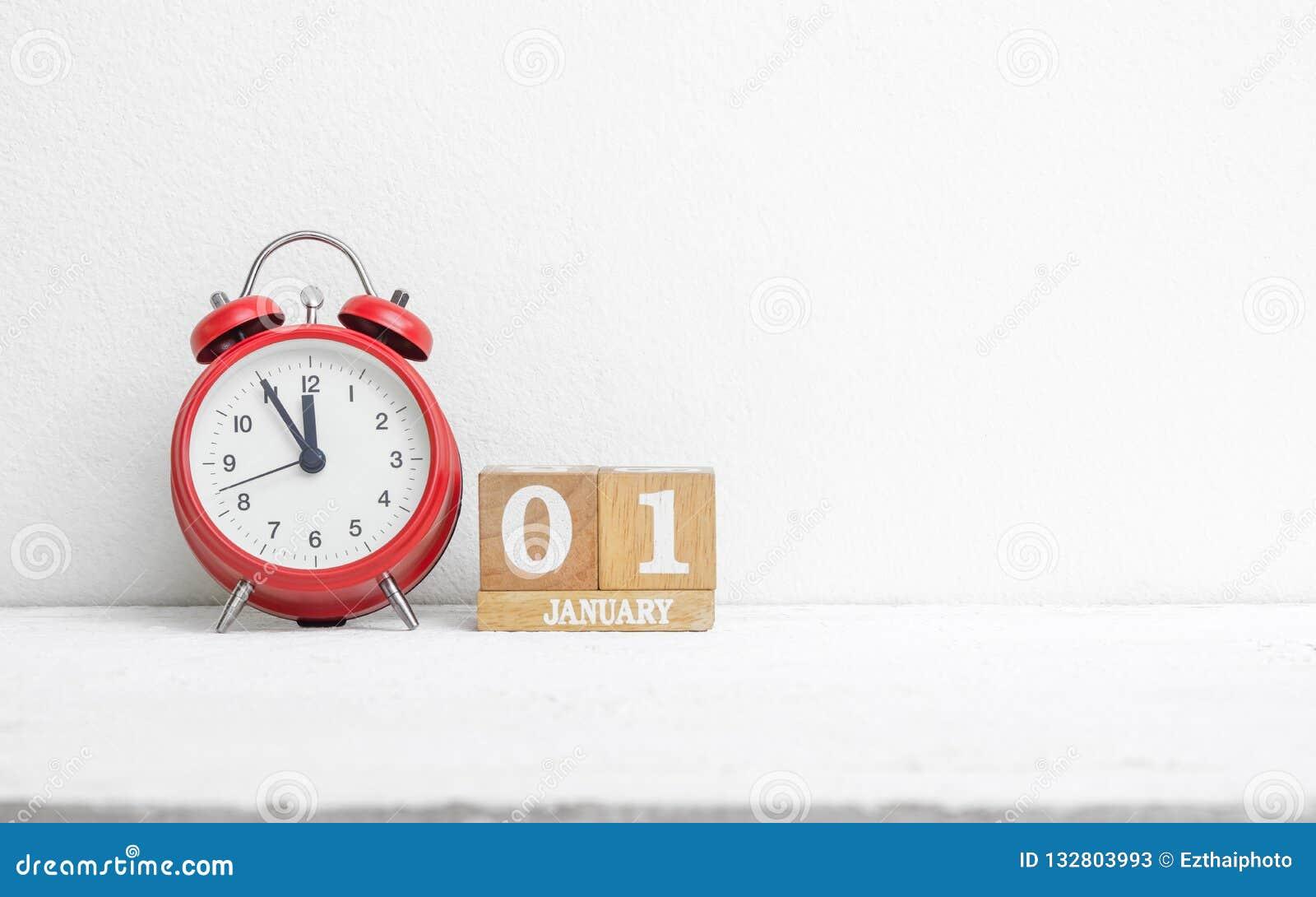 Chiuda su data di calendario del 1° gennaio di legno con la sveglia rossa