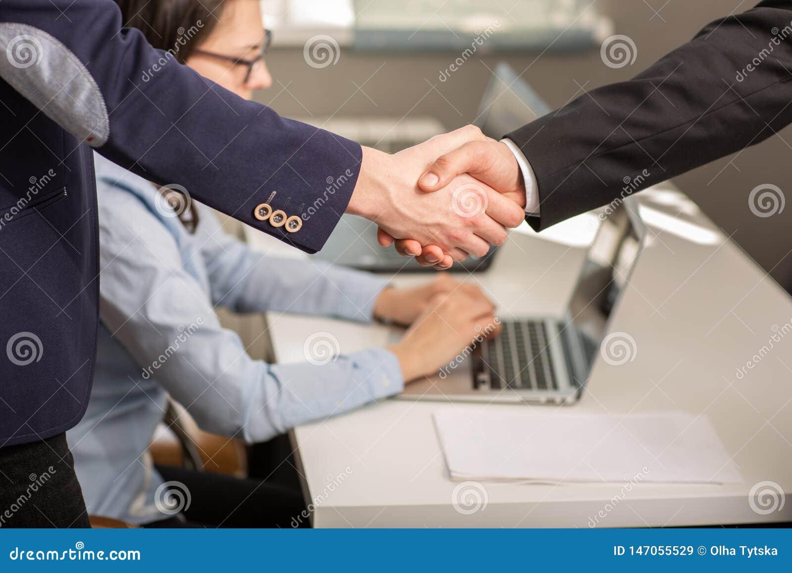 Chiuda su degli uomini d affari e dell associazione che stringono le mani per il progetto di accordo nel corso della riunione di