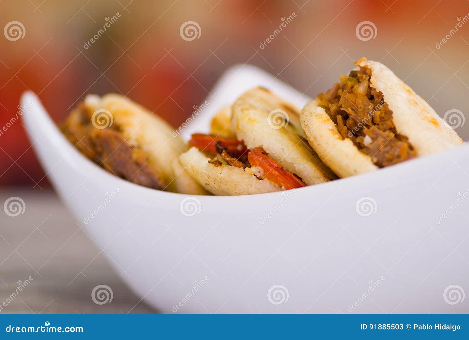 Chiuda su dei arepas deliziosi tradizionali, avocado del pollo e cheddar tagliuzzato ed il manzo tagliuzzato su di legno