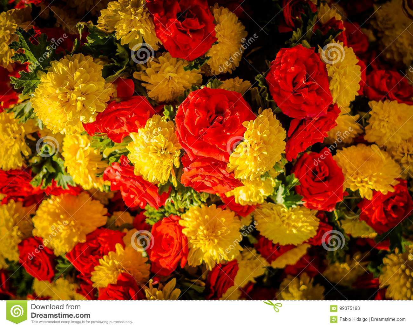 Chiuda su dei fiori gialli e rossi al mercato del Kr a Bangalore A Bangalore