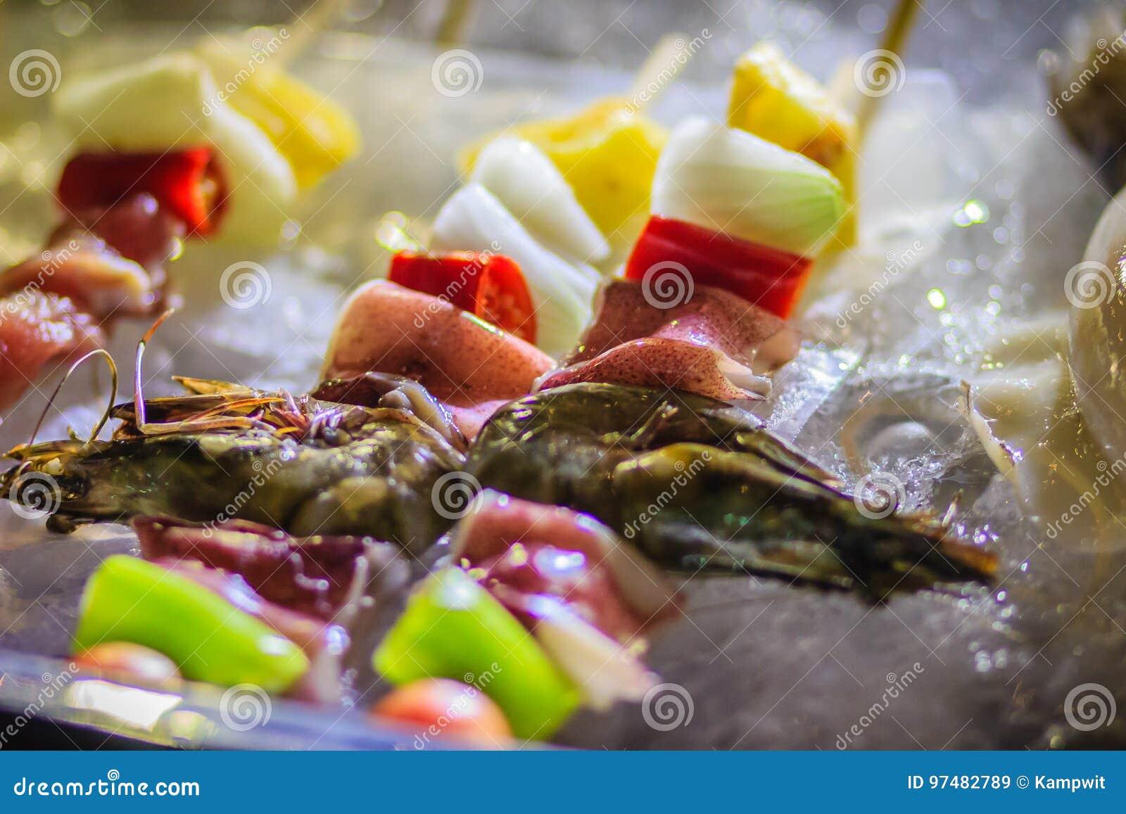 Chiuda su dei frutti di mare crudi e del barbecue della carne di maiale (BBQ) infilzati sulle sedere