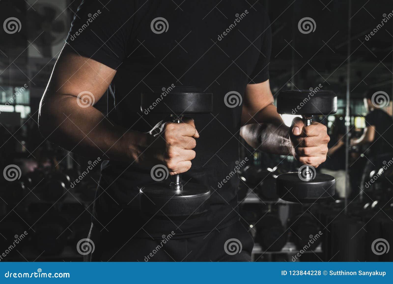 Chiuda su dei pesi di sollevamento muscolari di un giovane in palestra su fondo scuro