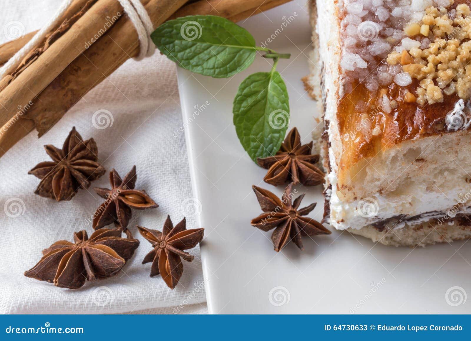 Chiuda su del dolce a sezione circolare con lo zucchero a velo, la crema, la menta, cinn