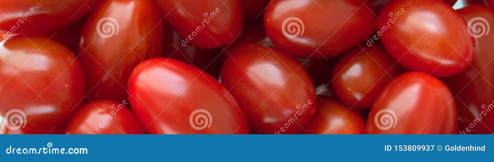 Chiuda su del gruppo di pomodori rossi freschi ad un mercato degli agricoltori Fondo organico del vegano