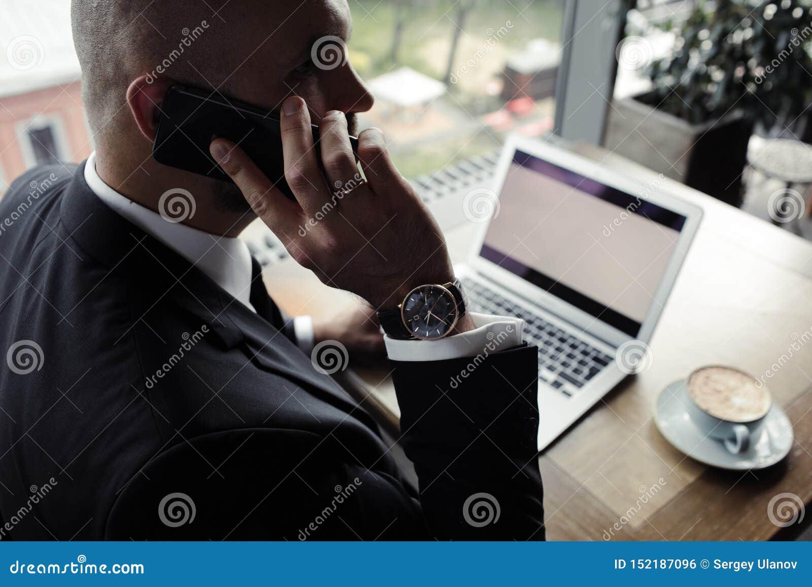Chiuda su dell uomo d affari bello, lavorando al computer portatile in ristorante