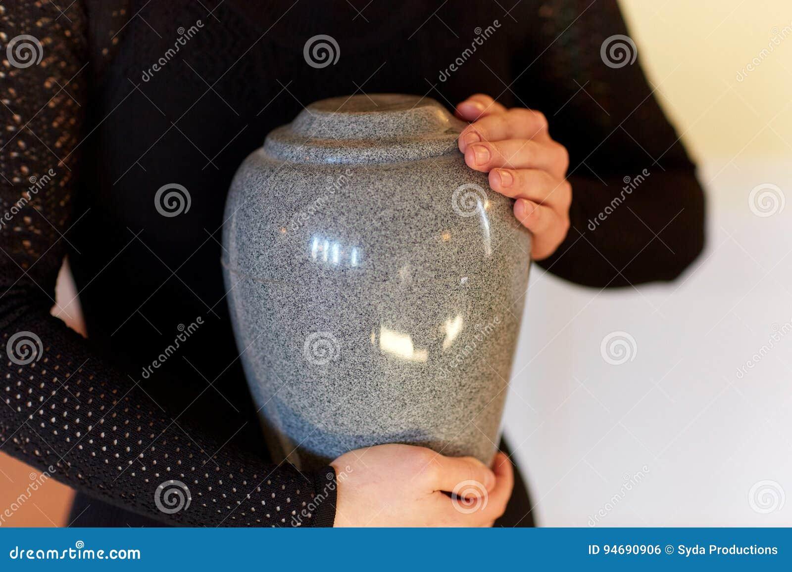 Chiuda su della donna con l urna di cremazione al funerale