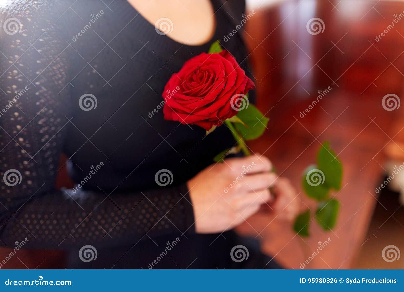 Chiuda su della donna con le rose al funerale in chiesa