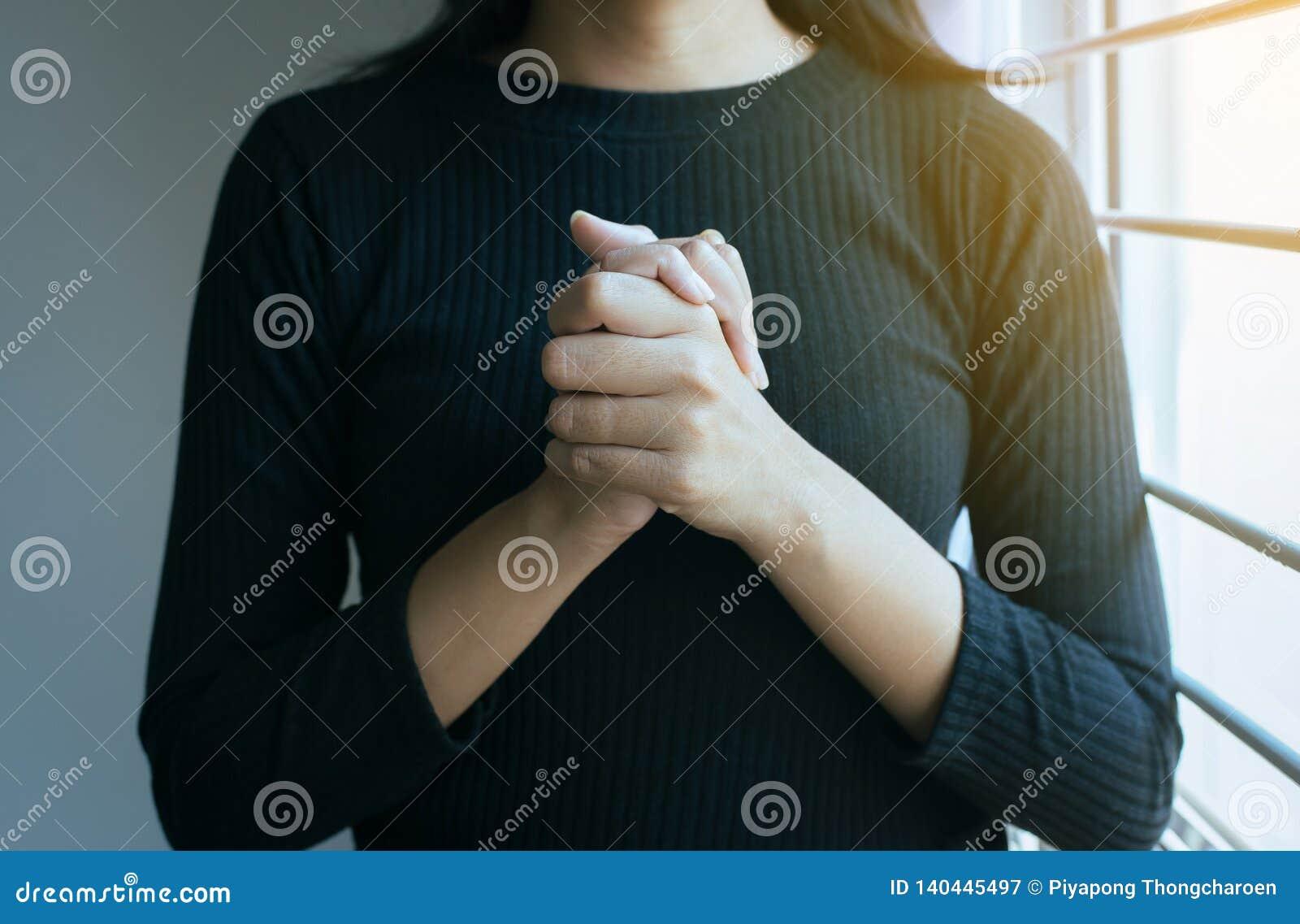 Chiuda su della donna della mano nel pregare la posizione, rispetto femminile di paga o posizioni le vostre mani insieme di pregh