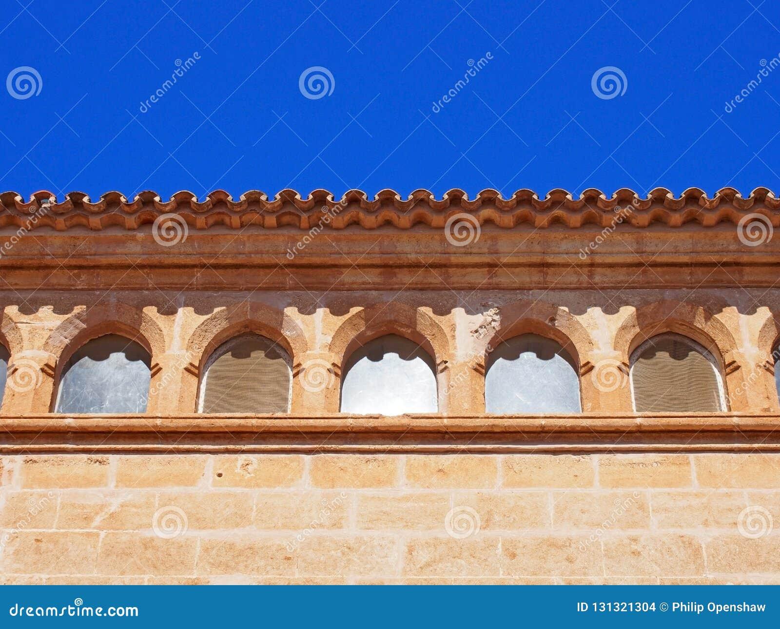 Chiuda su della linea del tetto di vecchia costruzione spagnola di pietra con le mattonelle curve e le finestre decorate con un c