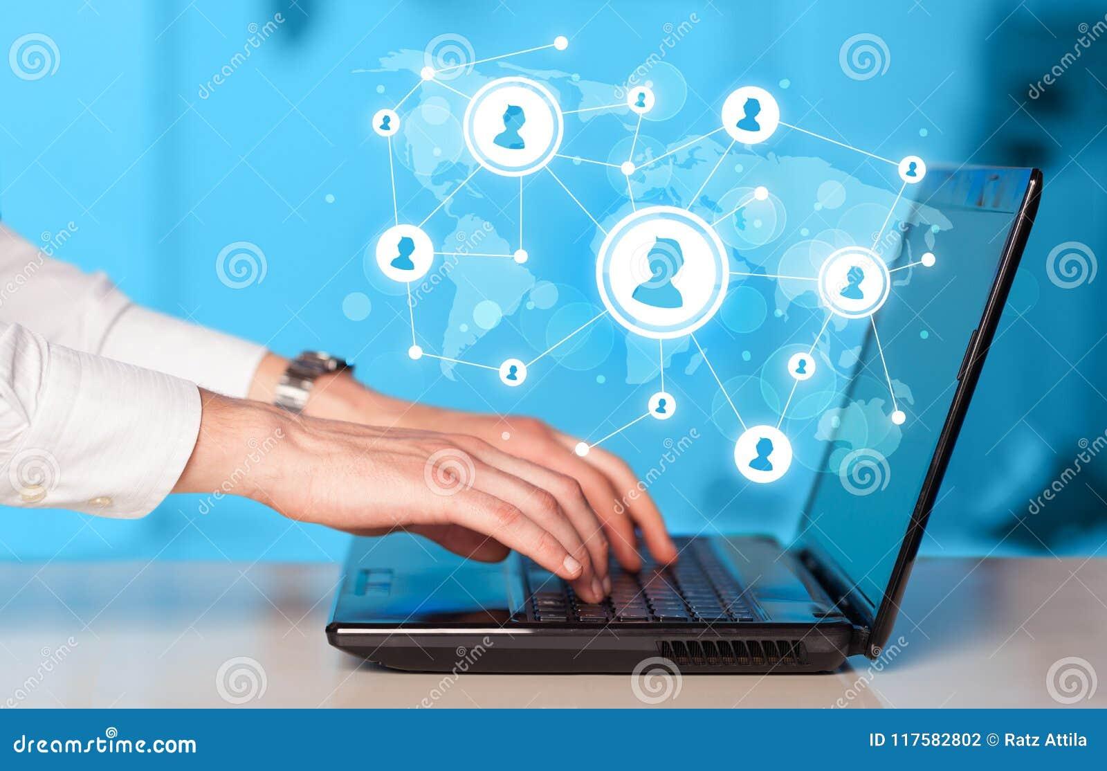 Chiuda su della mano con le icone di media del sociale e del computer portatile