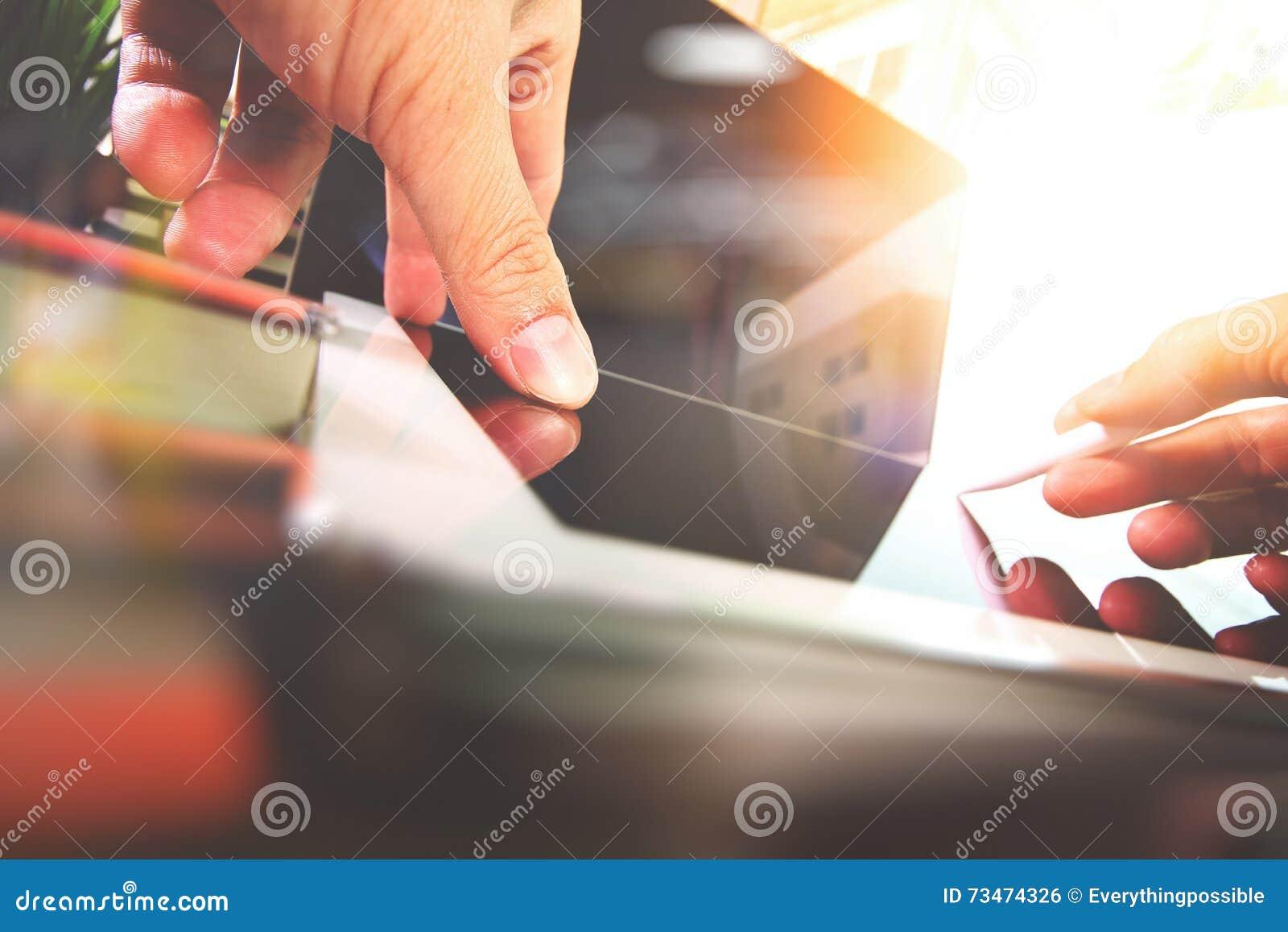 Chiuda su della mano del progettista che funziona con il computer portatile su di legno