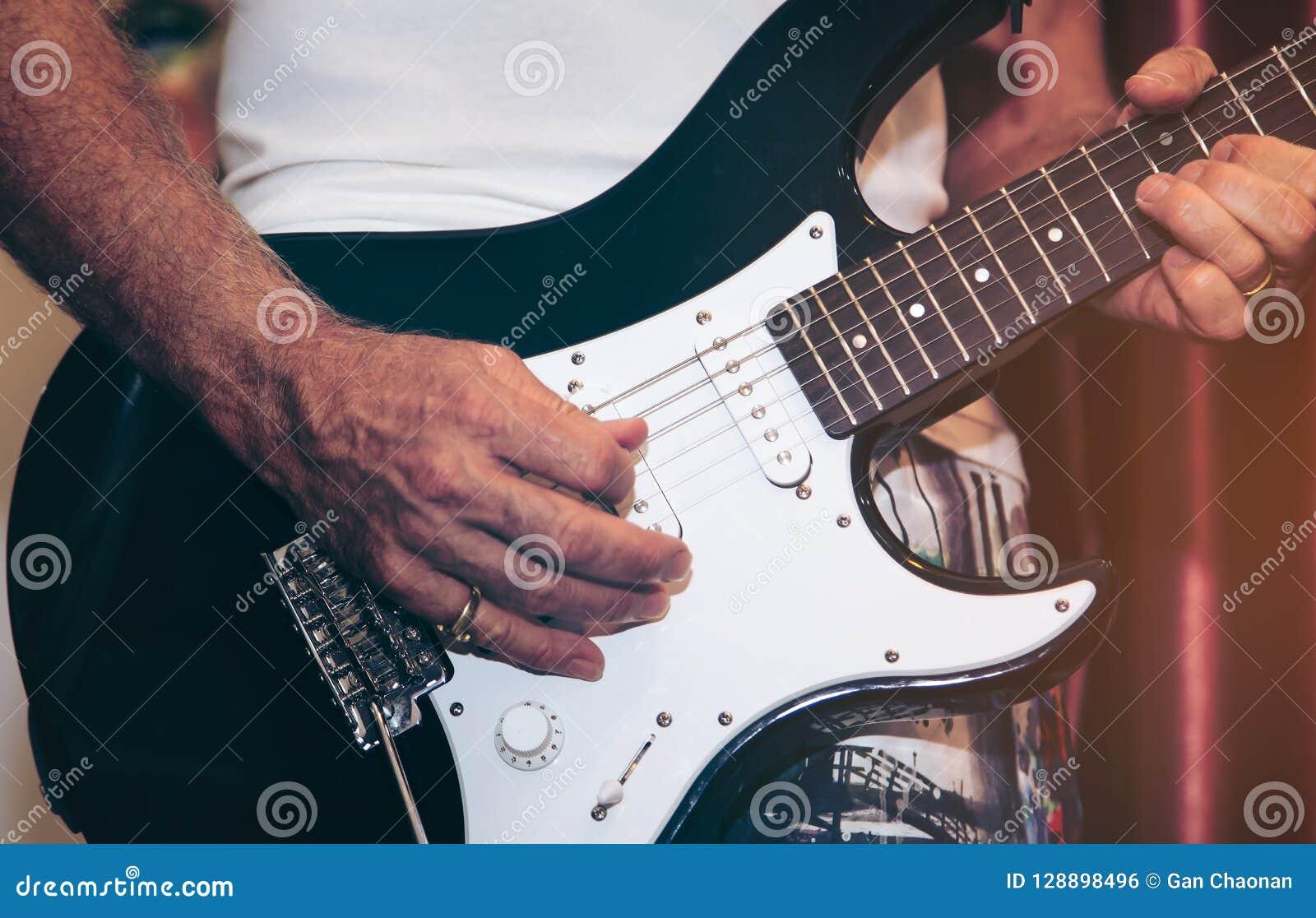 Chiuda su della mano dell uomo che gioca la chitarra in scena per fondo