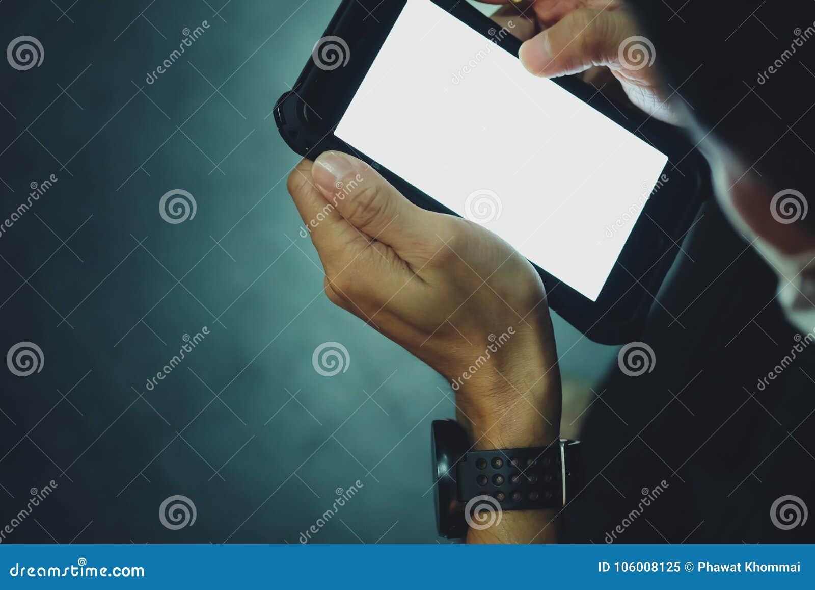 Chiuda su della mano dell uomo che utilizza gli Smart Phone mobili nello scuro