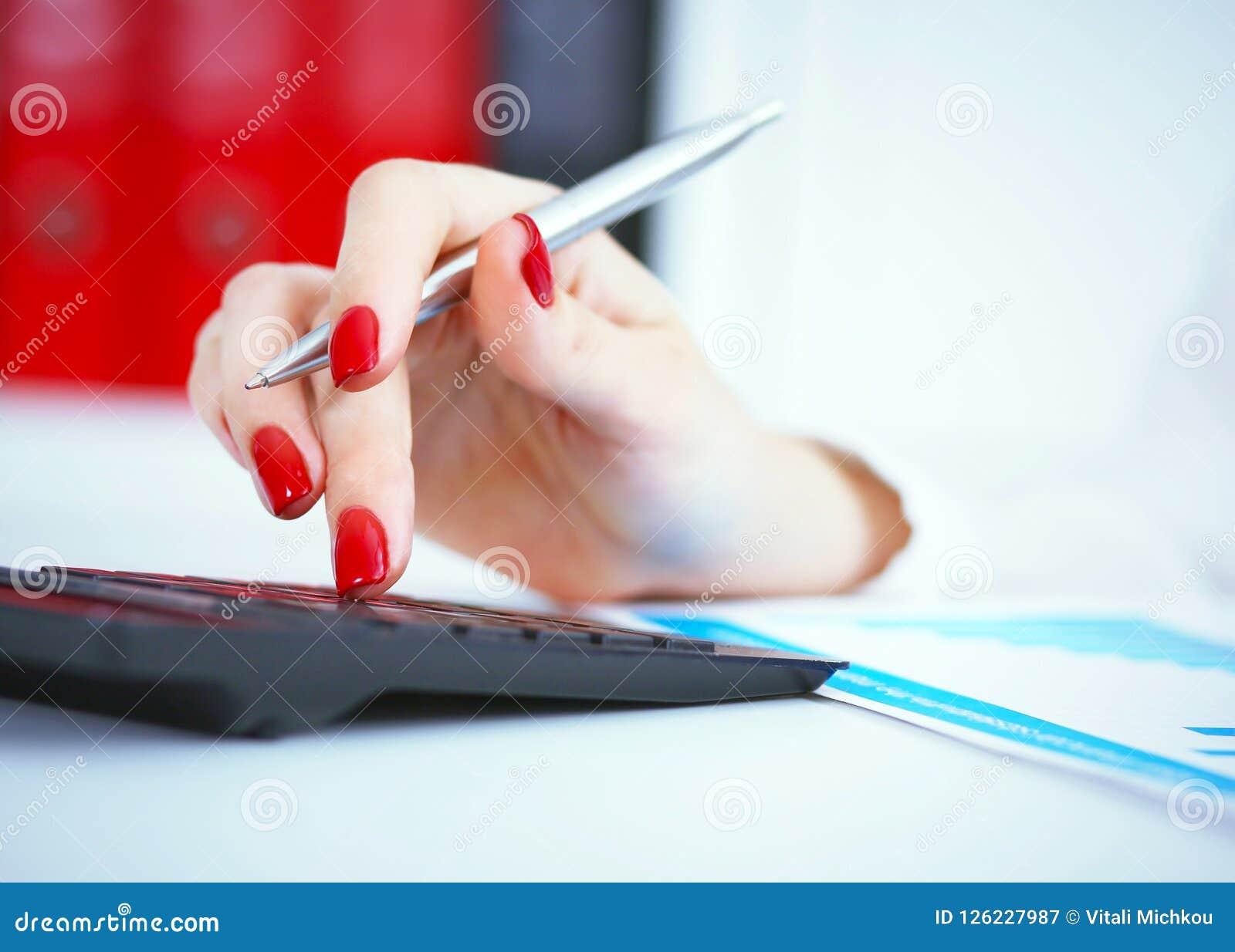 Chiuda su della mano femminile del banchiere o del ragioniere che effettua i calcoli Risparmio, finanze e concetto di economia