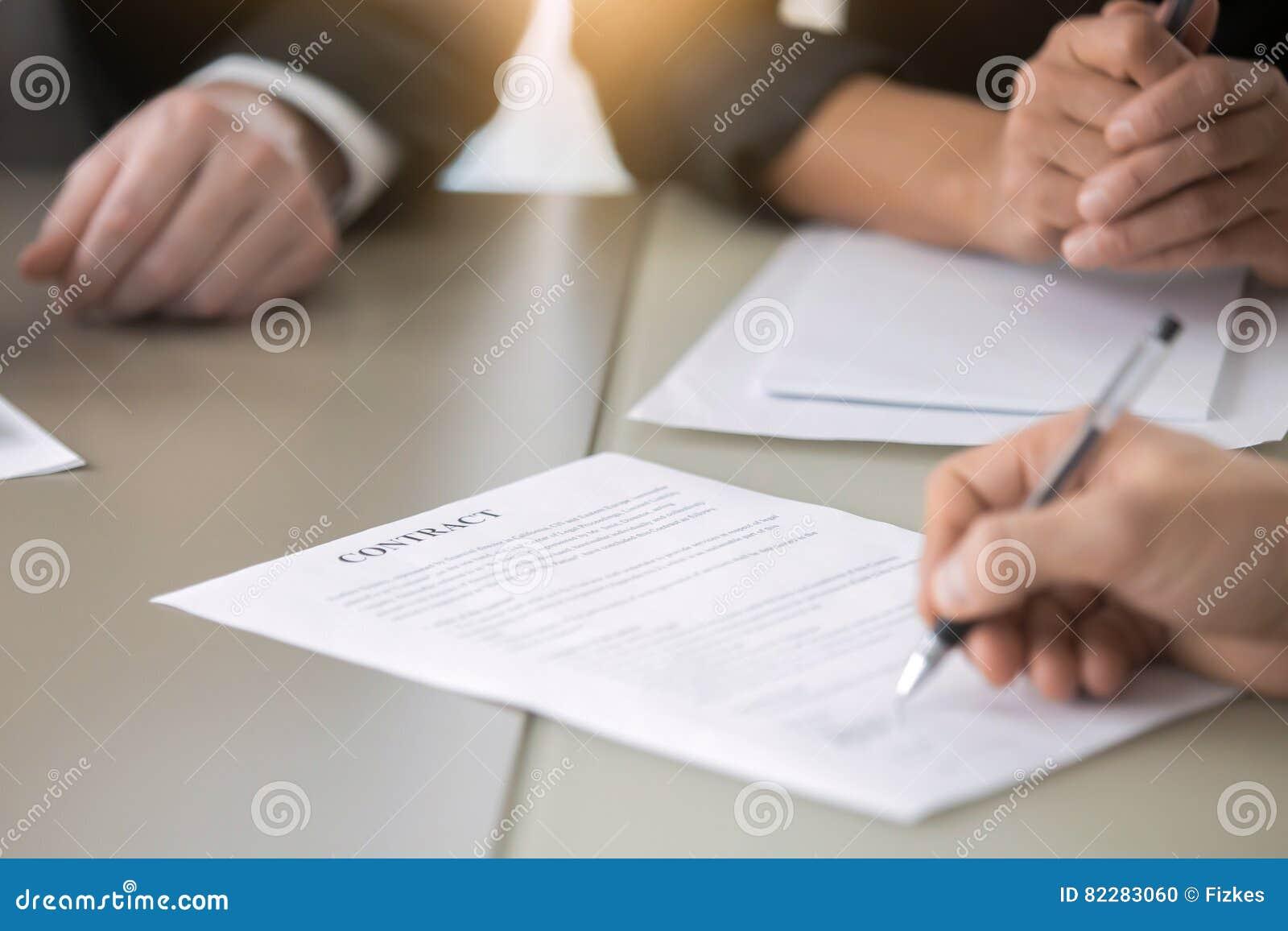 Chiuda su della mano maschio che mette la firma in un contratto