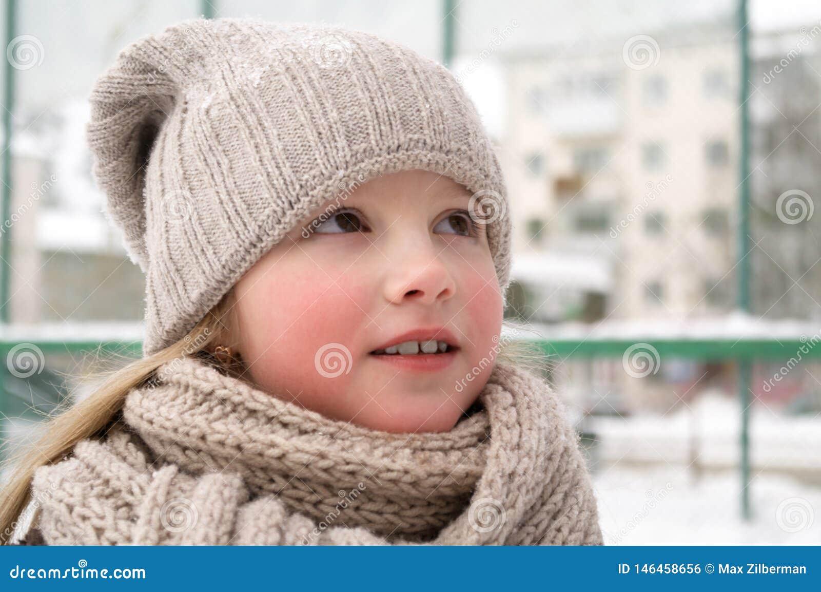 Chiuda su della ragazza sveglia sorridente con il cappello tricottato l inverno Colpo all aperto con fondo vago unfocused