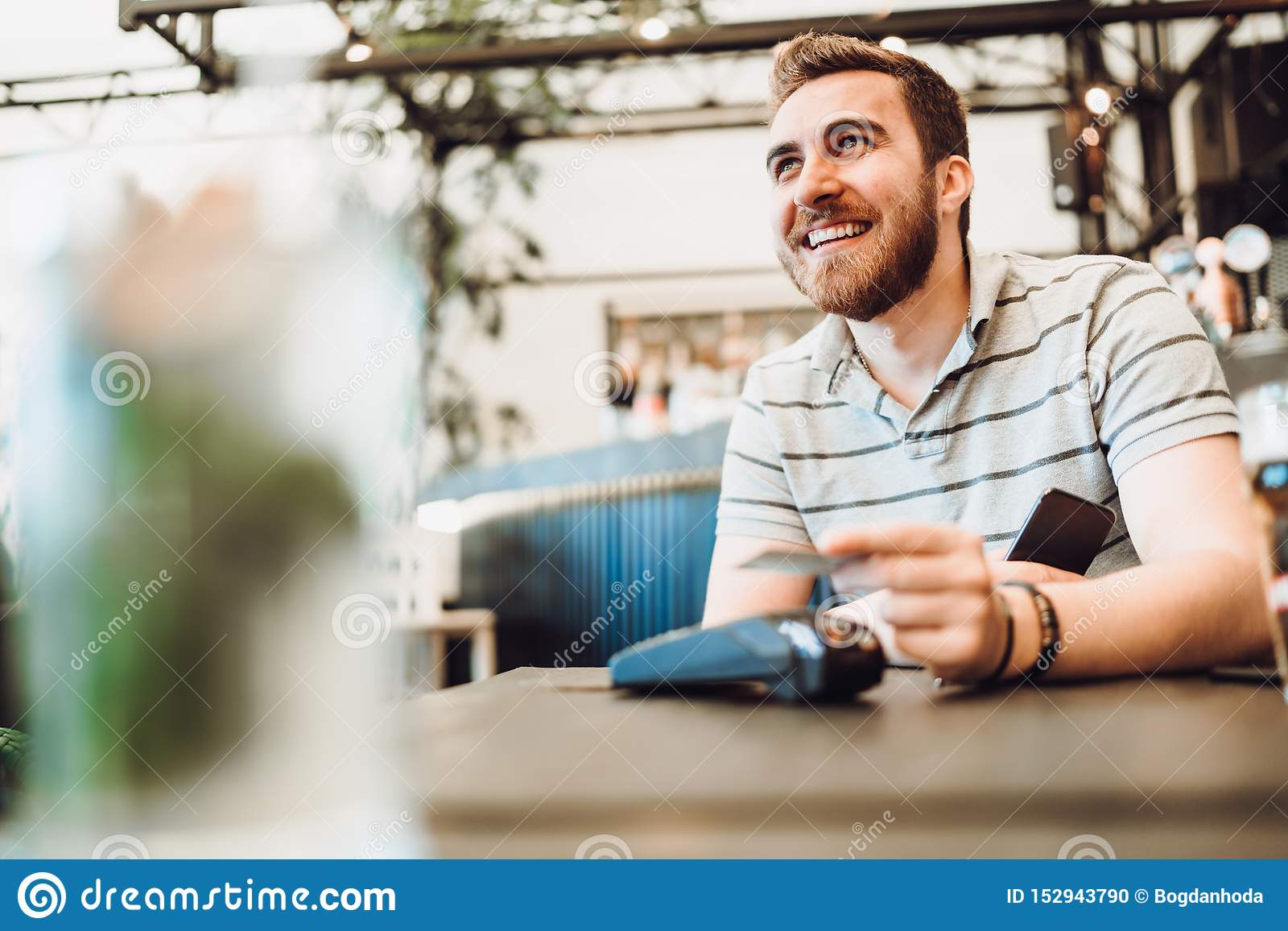 Chiuda su della tecnologia senza contatto usando maschio e dello smartphone della carta di credito per il pagamento nel ristorant