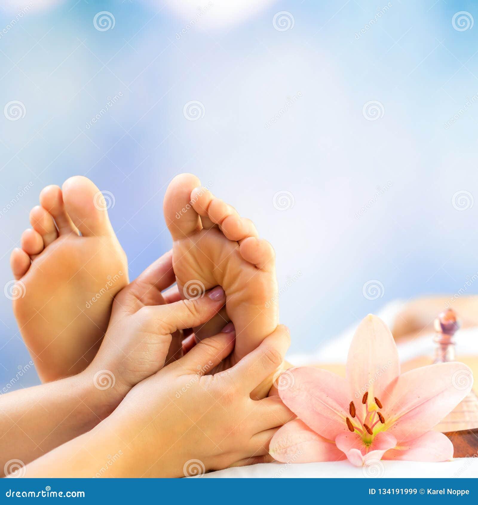 Chiuda su delle mani che fanno il trattamento di reflessologia sui piedi in stazione termale