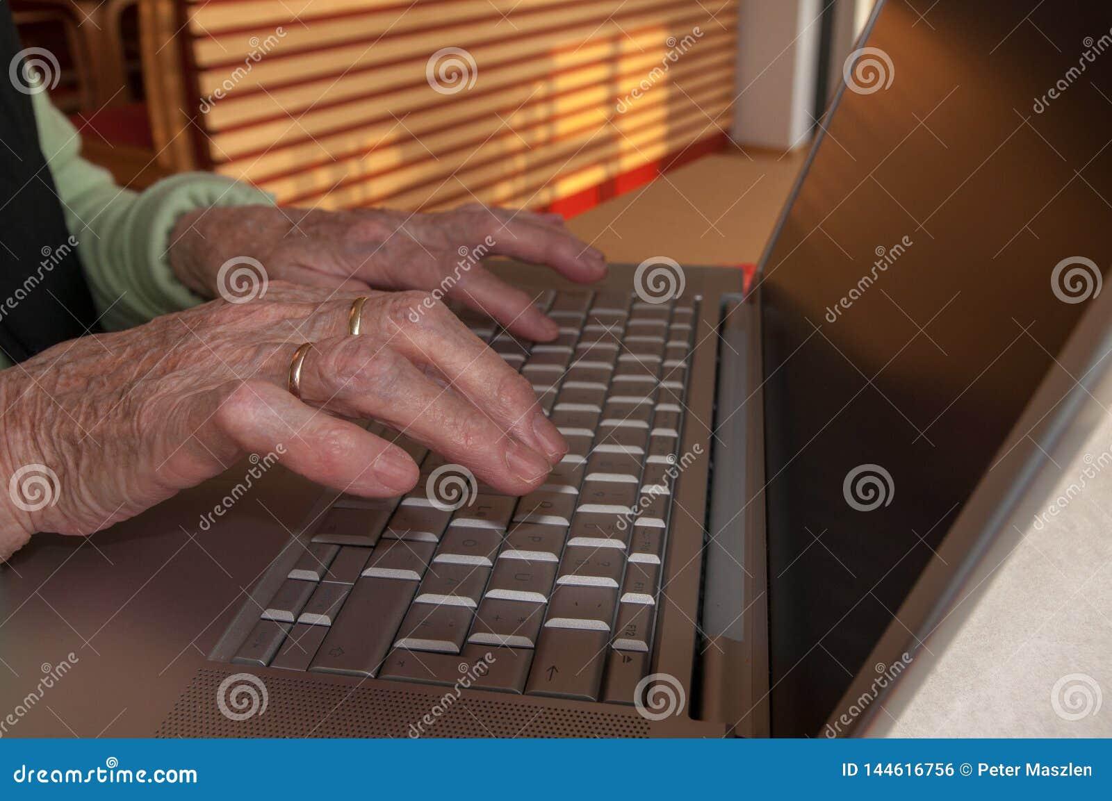 Chiuda su delle mani della donna senior che lavorano alla tastiera di computer