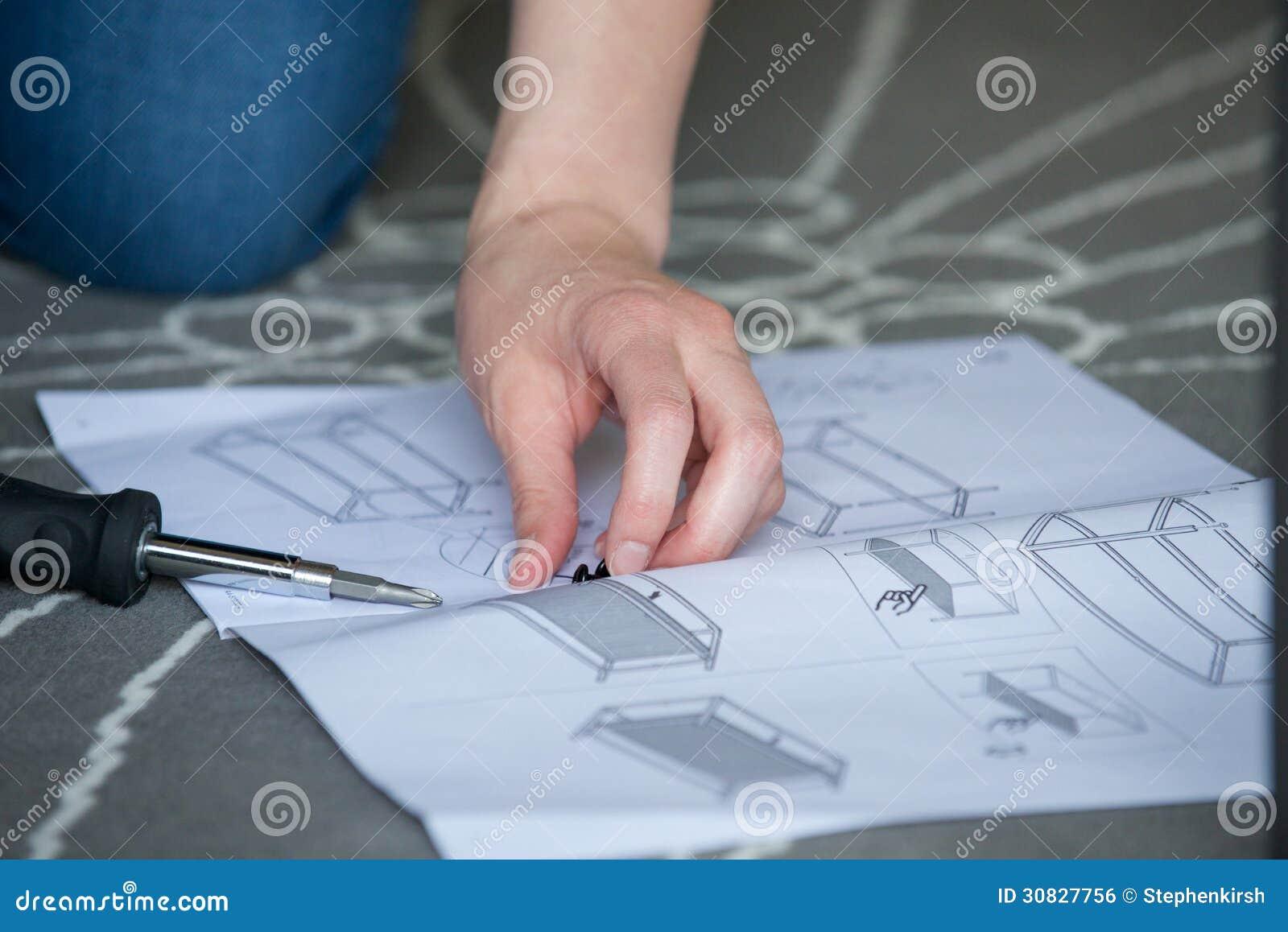 Chiuda su delle mani, gli scerws, le istruzioni per mobili metallici