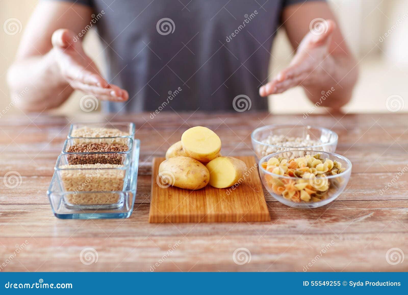 Chiuda su delle mani maschii con l alimento del carboidrato