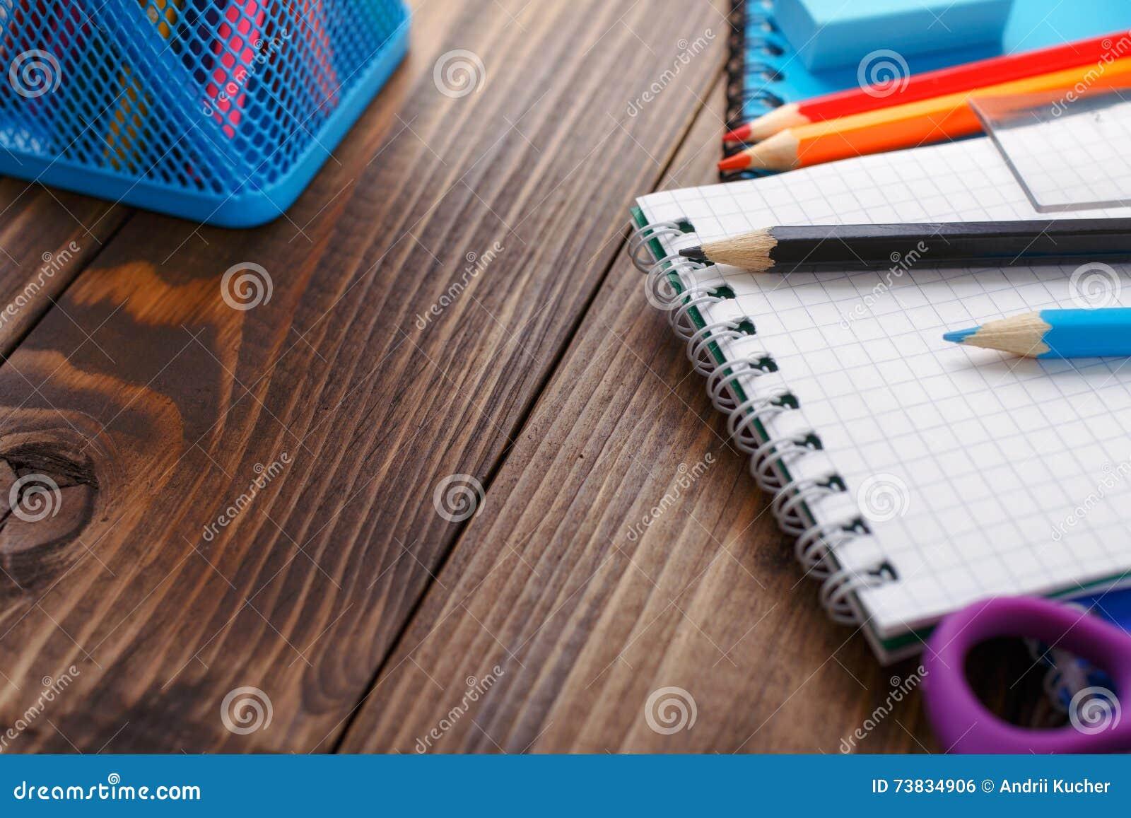 Chiuda su delle matite colorate con un taccuino