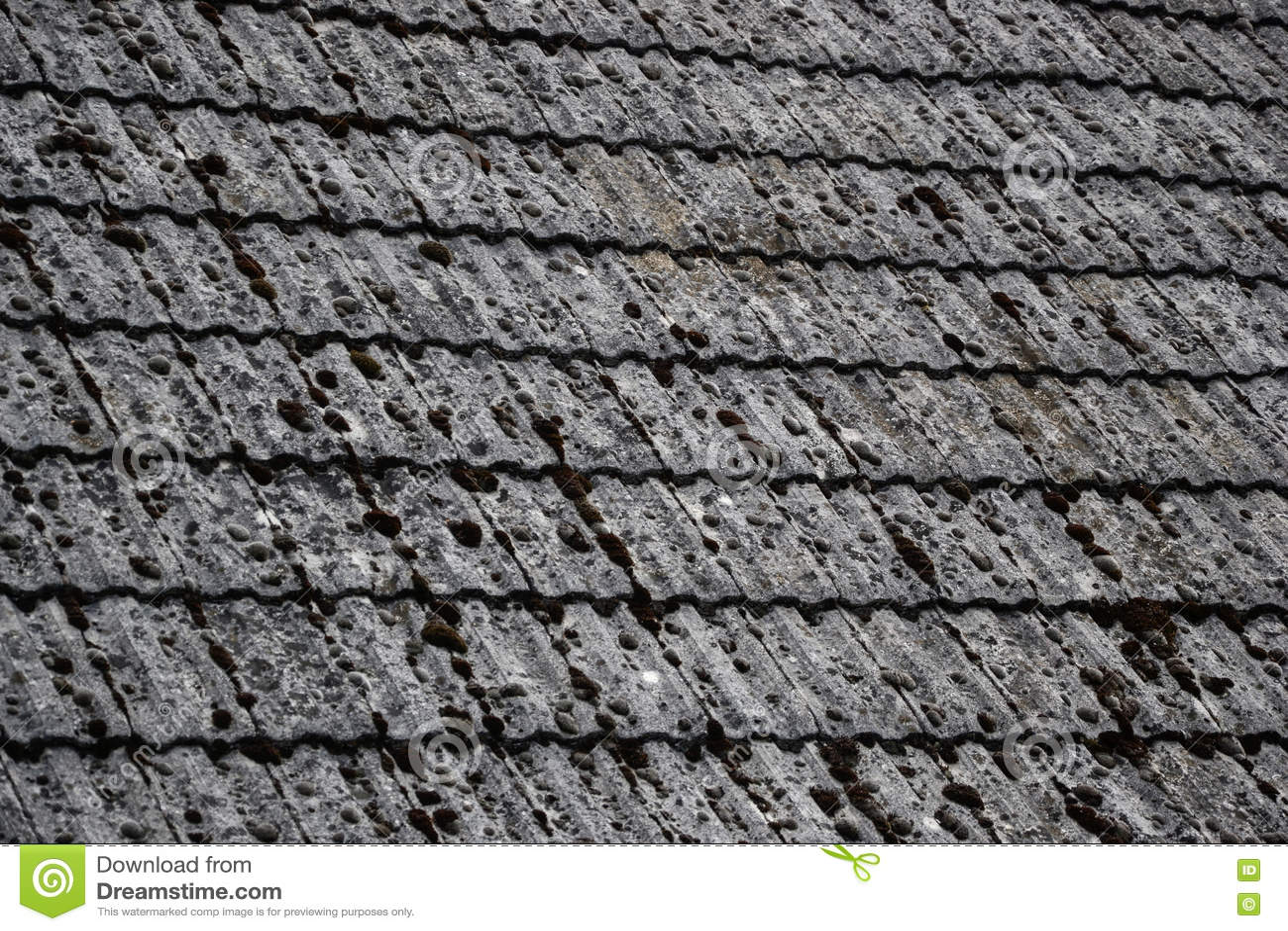 Chiuda su delle mattonelle di tetto invecchiate sulla vecchia casa