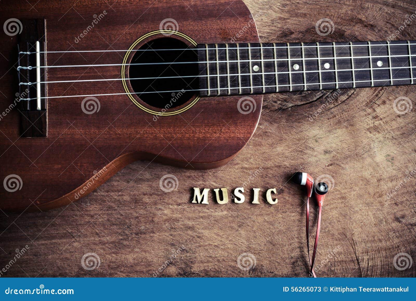 Chiuda su delle ukulele e del trasduttore auricolare su vecchio fondo di legno