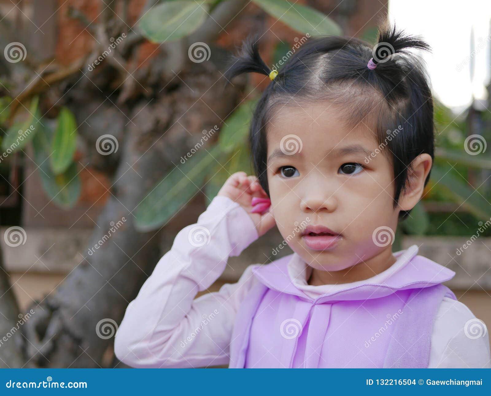 Chiuda su di poco asiatico, tailandese, neonata, mettente un fiore dietro il suo orecchio