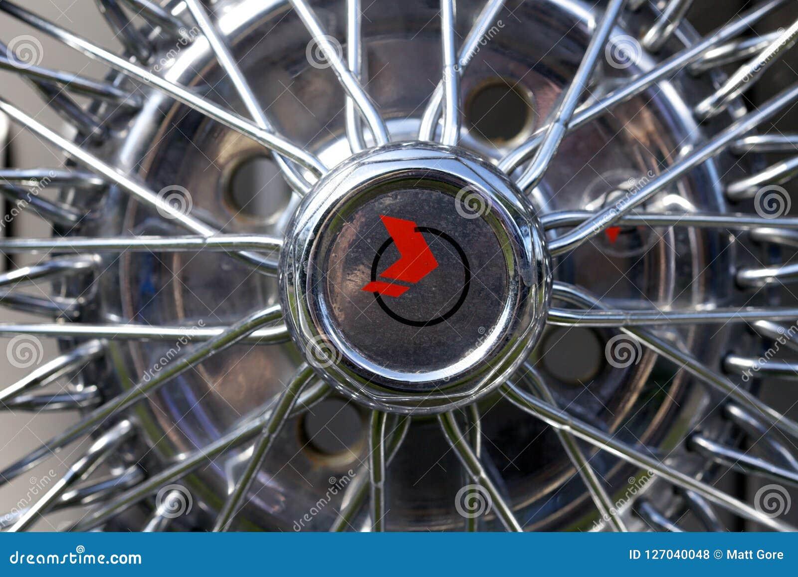 Chiuda su di un cappuccio di hub della ruota del raggio del cromo su un automobile classica