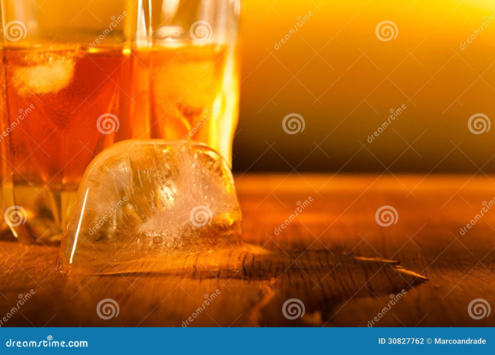 Chiuda su di un cubetto di ghiaccio che si fonde con una bevanda