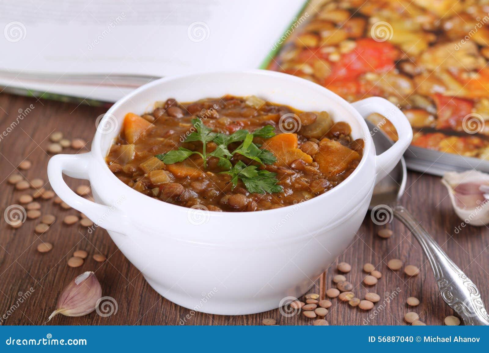 Chiuda su di una ciotola di minestra di lenticchia guarnita con prezzemolo