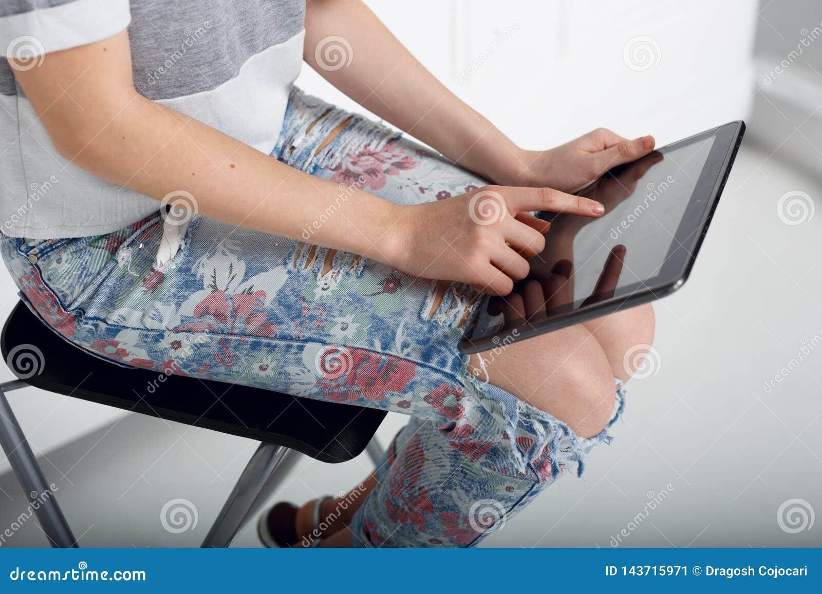 Chiuda su di una ragazza che tiene sul suo ginocchio una compressa e tocchi lo schermo con il dito Stampe della mano sulla compre
