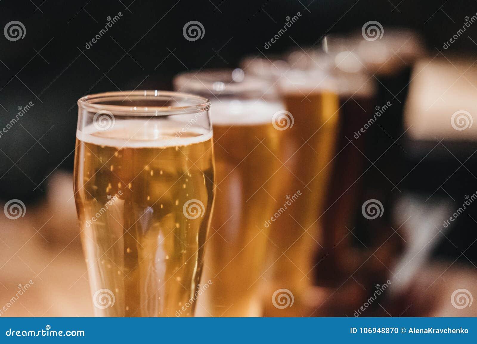 Chiuda su di uno scaffale dei generi differenti di birre, scuri per accendersi, su una tavola
