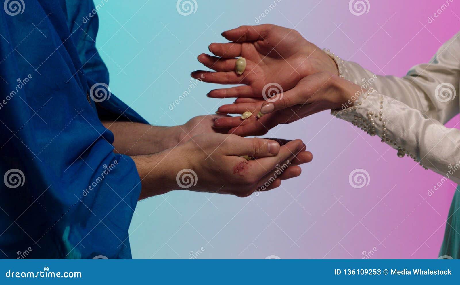Chiuda su per le mani orientali della giovane donna che danno molte piccole conchiglie alle mani dell uomo, concetto di baratto a