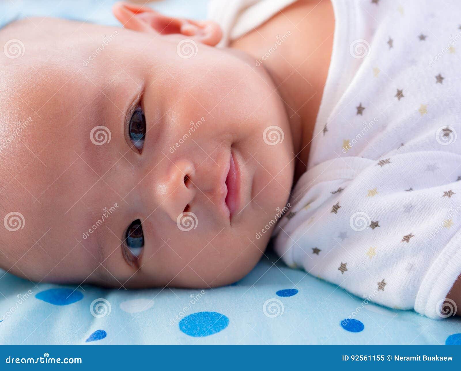Chiuda su, sorridere asiatico del neonato