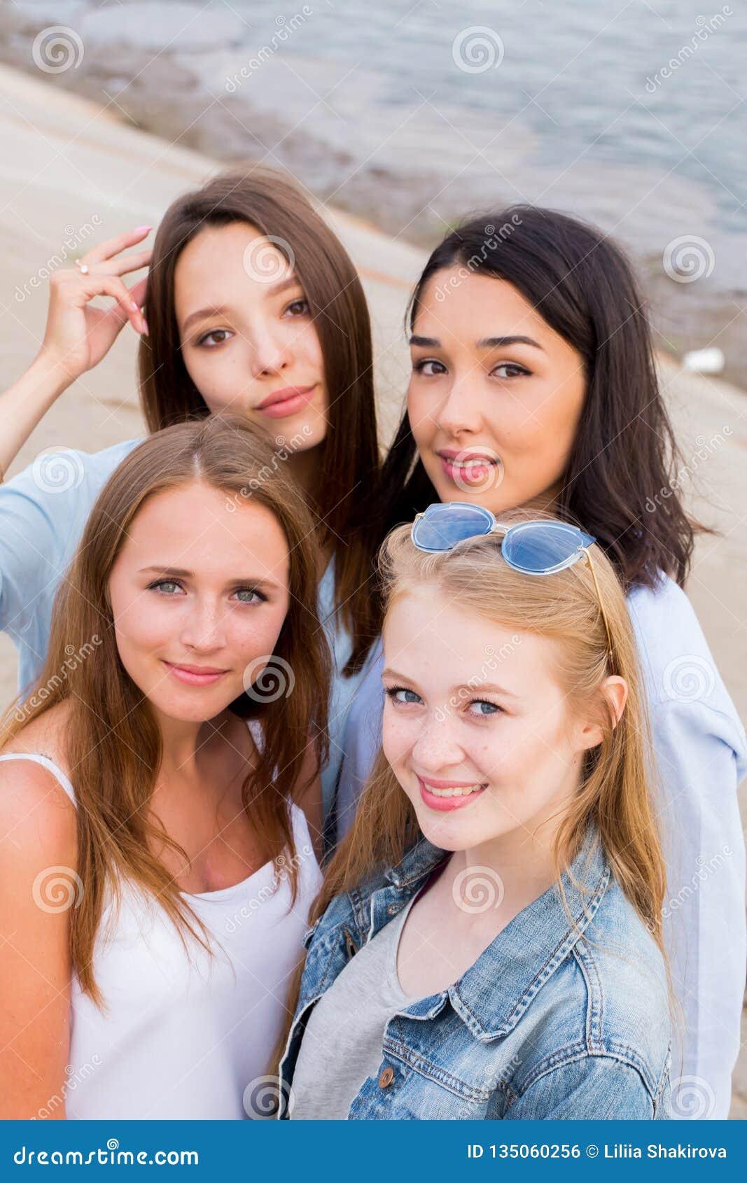 Chiuda su un ritratto di quattro giovani belle amiche di estate sulla spiaggia