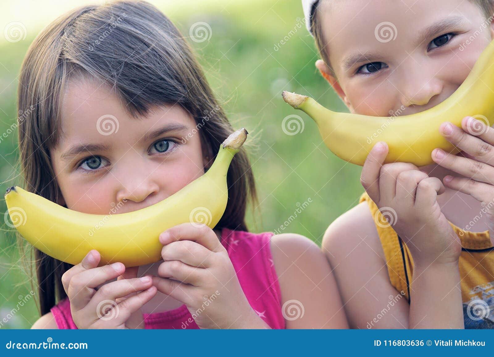 Chiuda sui fronti di bei giovani ragazza e ragazzo caucasici con il sorriso della banana sul fondo della natura