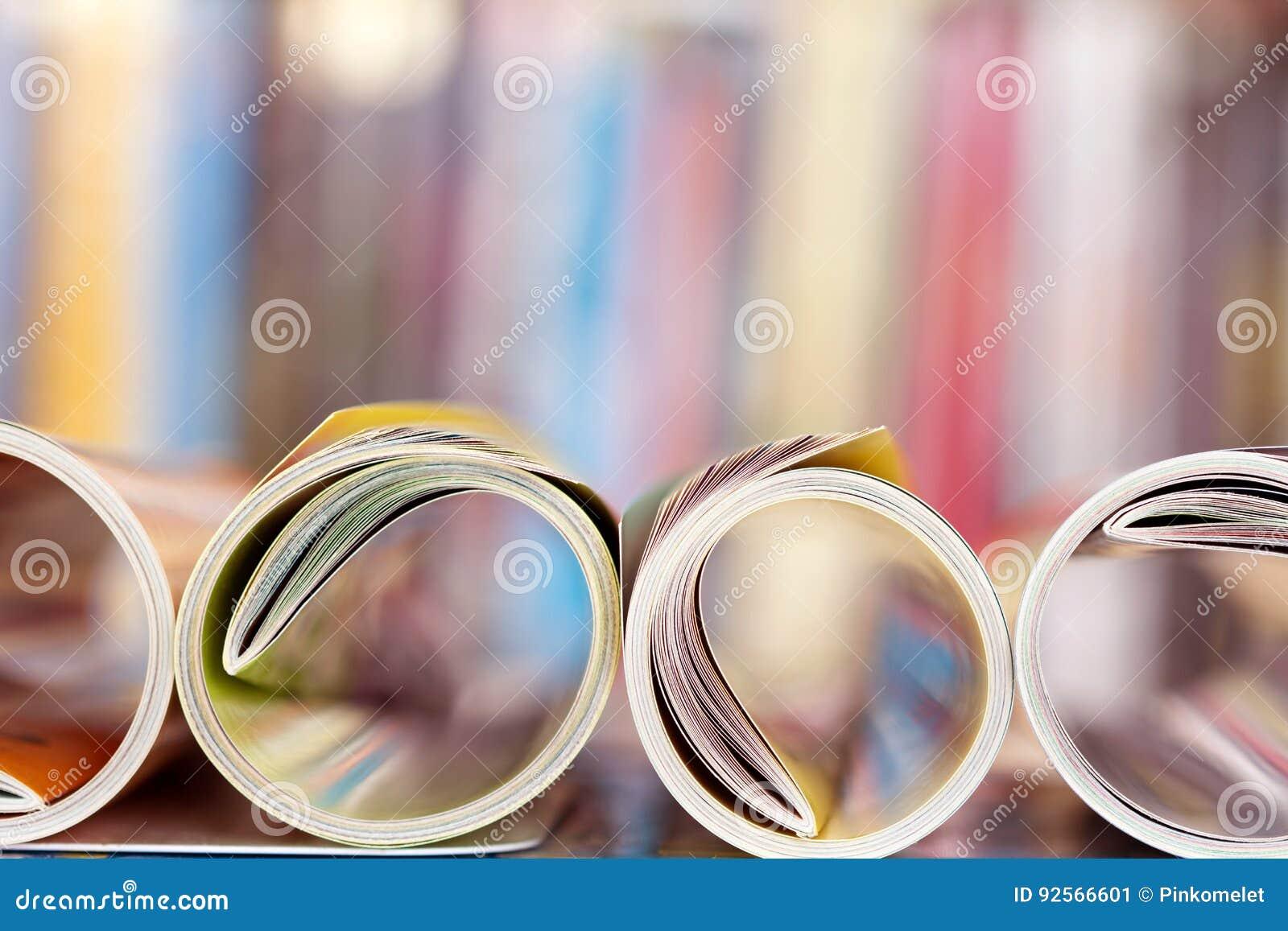 Chiuda sul bordo della rivista variopinta che impila il rotolo con la BO confusa
