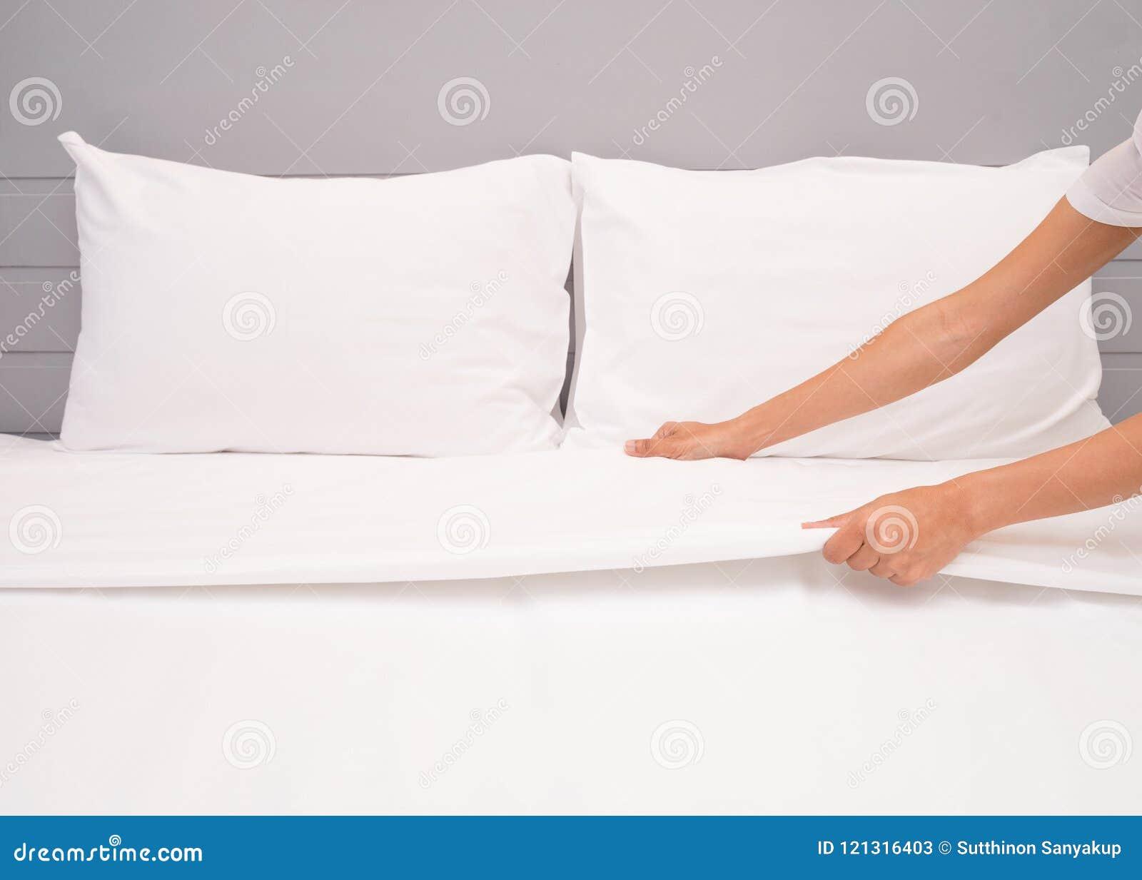 Chiuda sul lenzuolo bianco installato mano nella camera di albergo