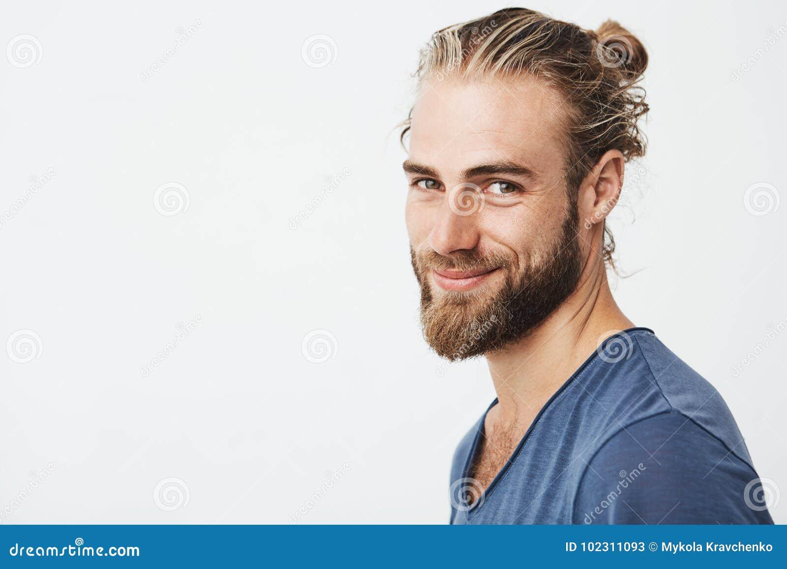 Chiuda sul ritratto del tipo virile bello con la barba che posa in tre quarti, guardante in camera e sorridente felicemente