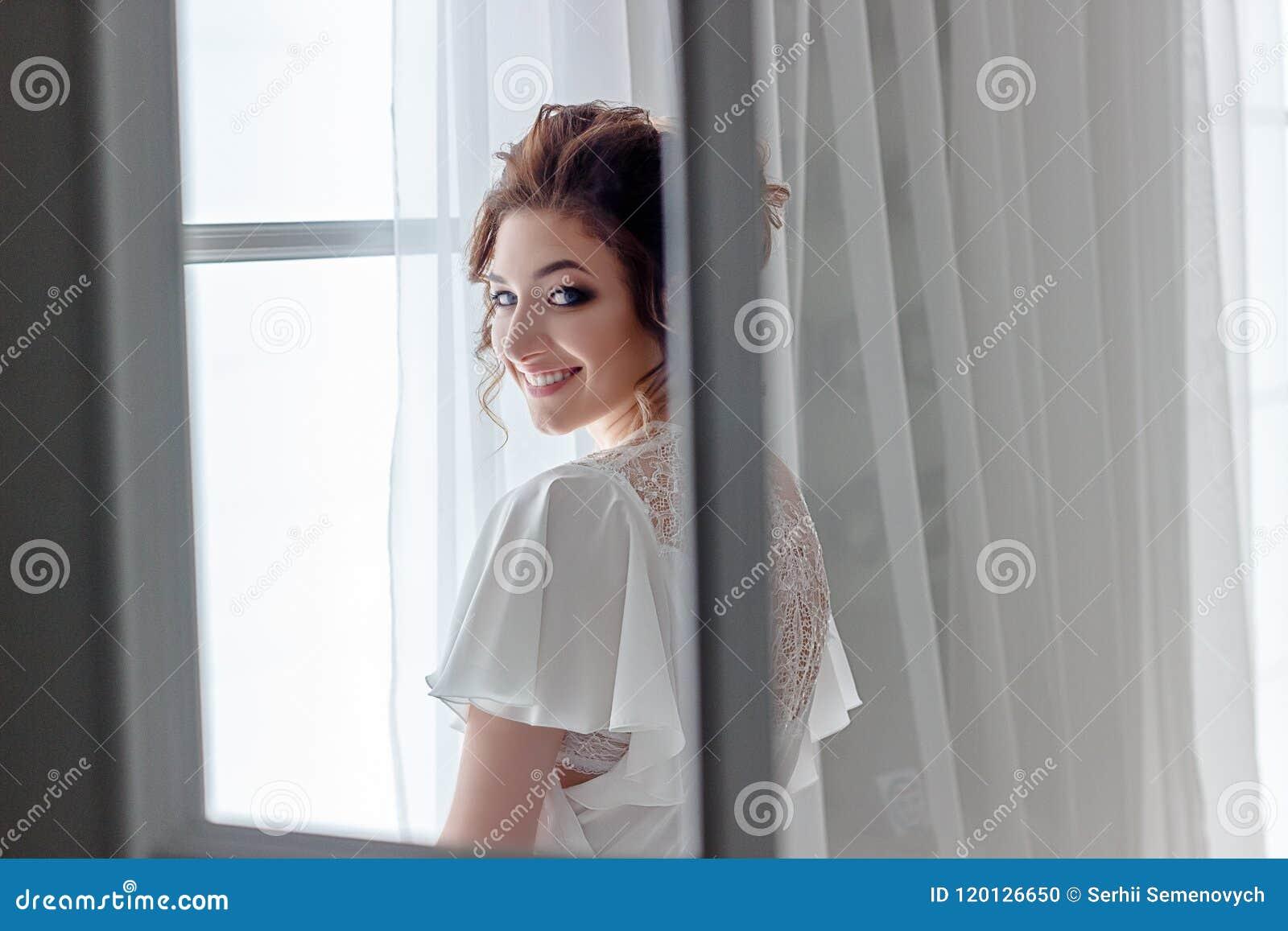 Chiuda sul ritratto di bella giovane signora che si rilassa alla finestra ed alla macchina fotografica di sguardo felice