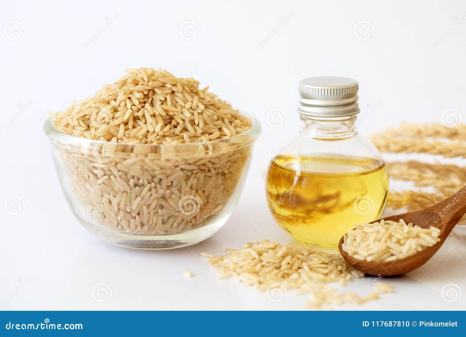 Chiuda sul seme del riso sbramato e sull olio della crusca di riso in bottiglia e riso non macinato su fondo bianco, buoni grassi