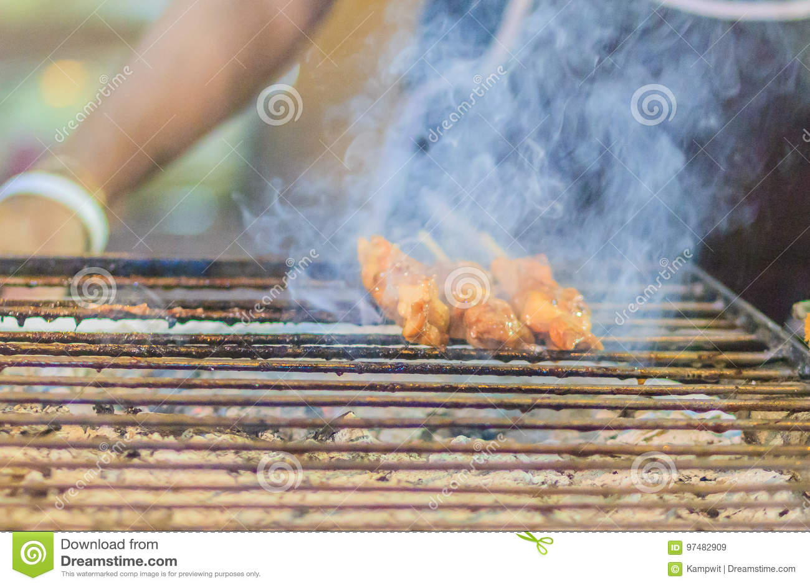 Chiuda sul venditore che griglia la carne di maiale satay nel fumo, bistecca tailandese