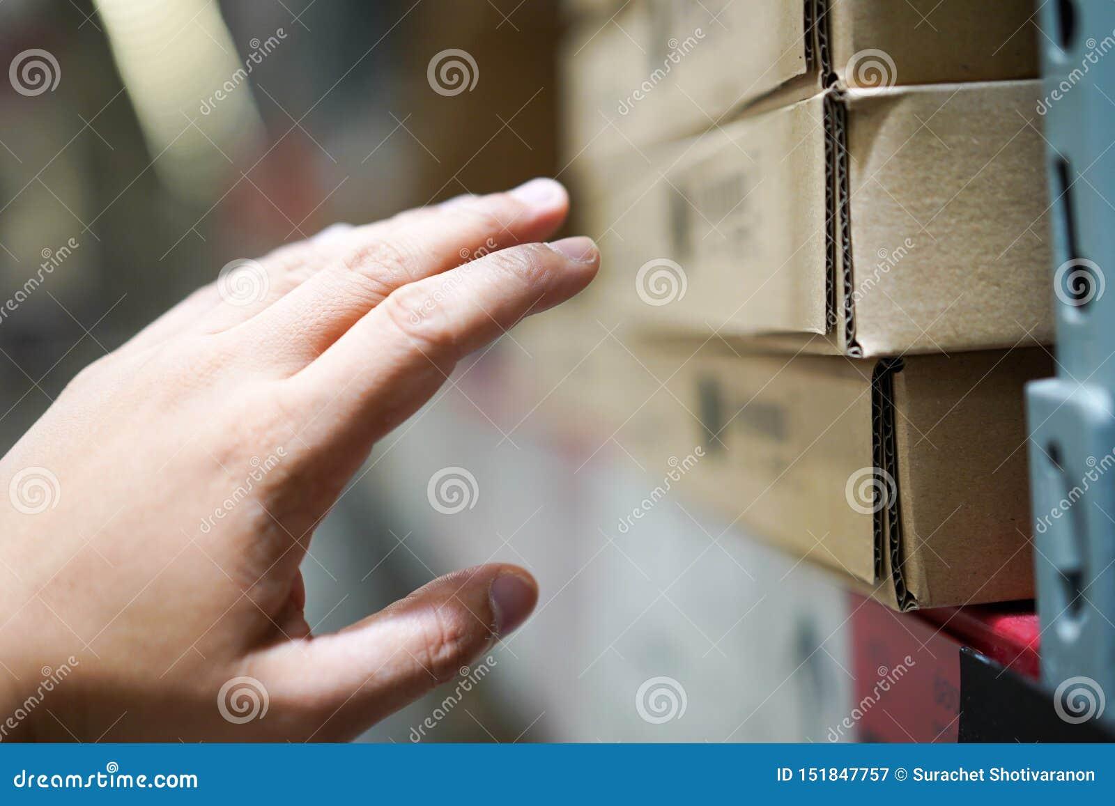 Chiuda sull uomo che raggiunge la sua mano a mobilia in una scatola di carta marrone sullo scaffale nel magazzino