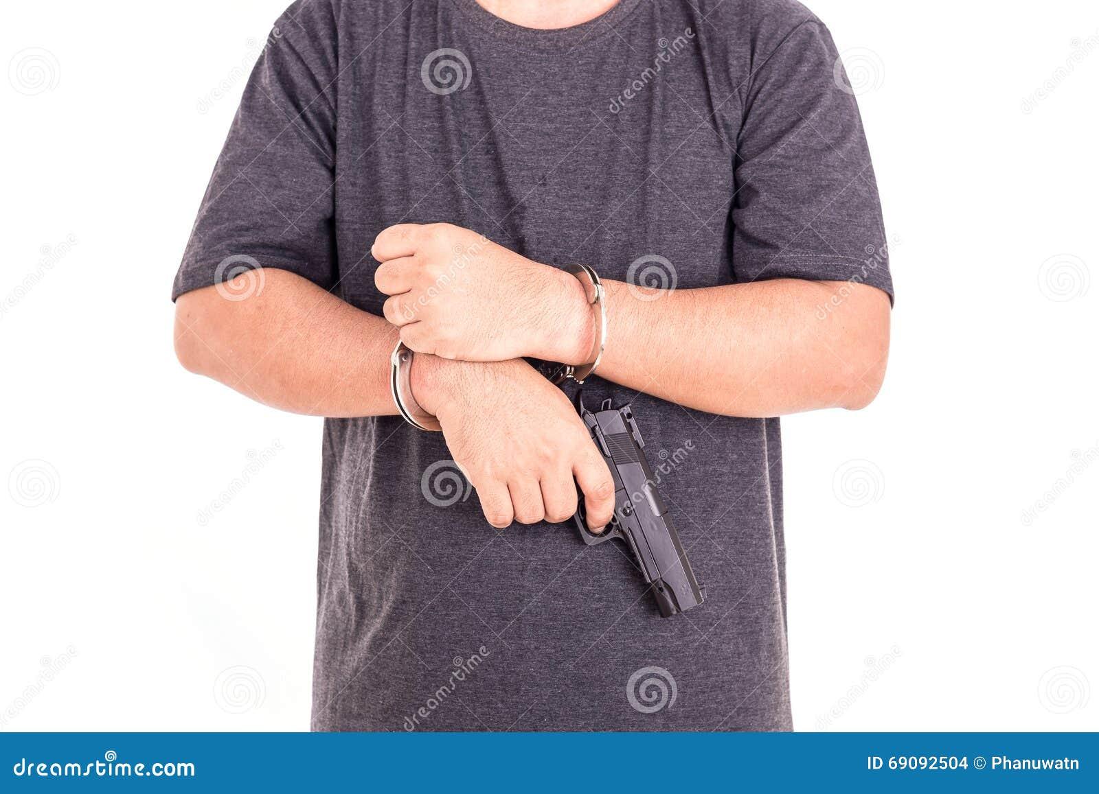 Chiuda sull uomo con le manette e la pistola sulle mani isolate su bianco
