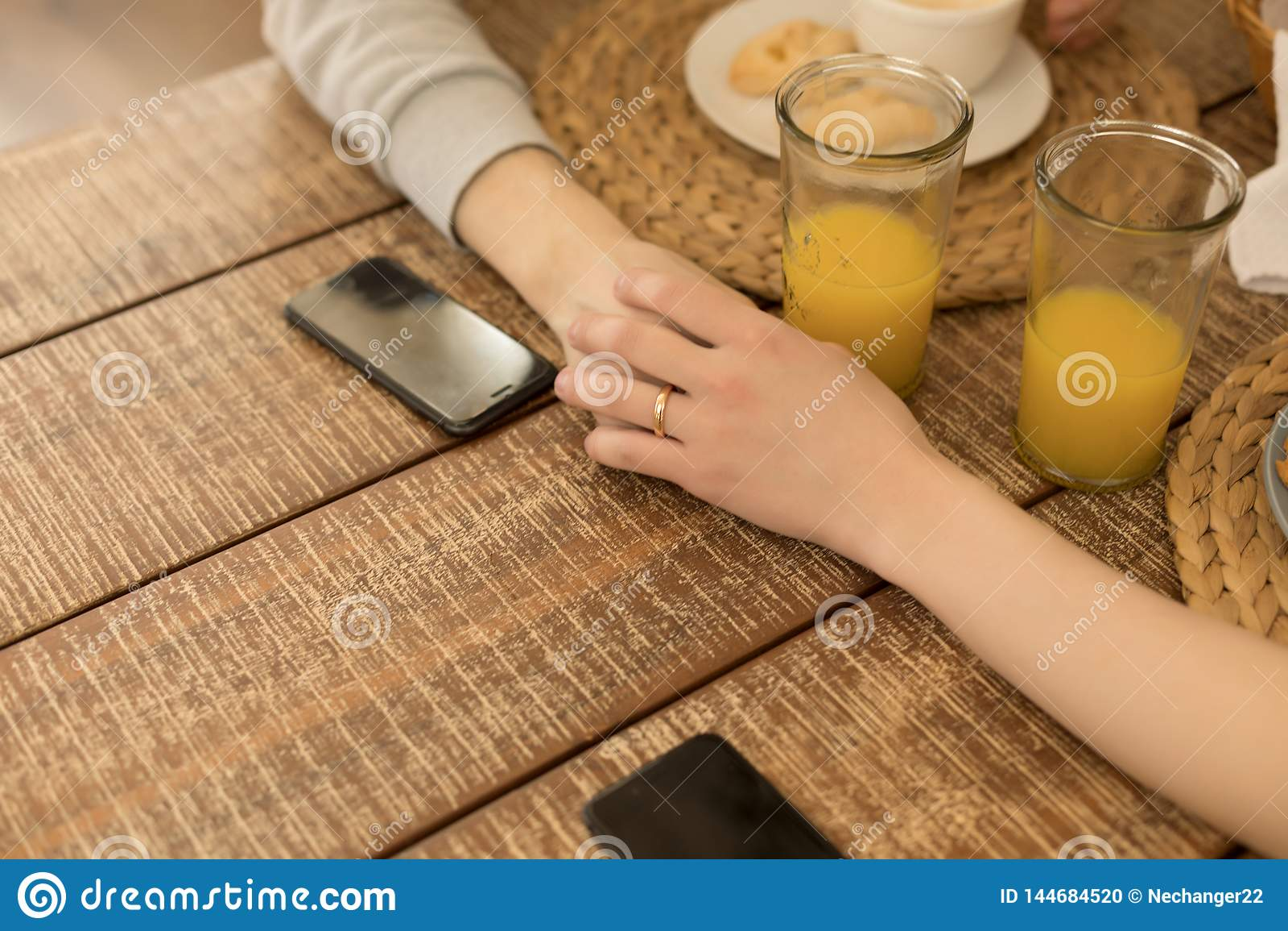 Chiuda sulla foto Due omosessuali che si tengono per mano insieme alla tavola