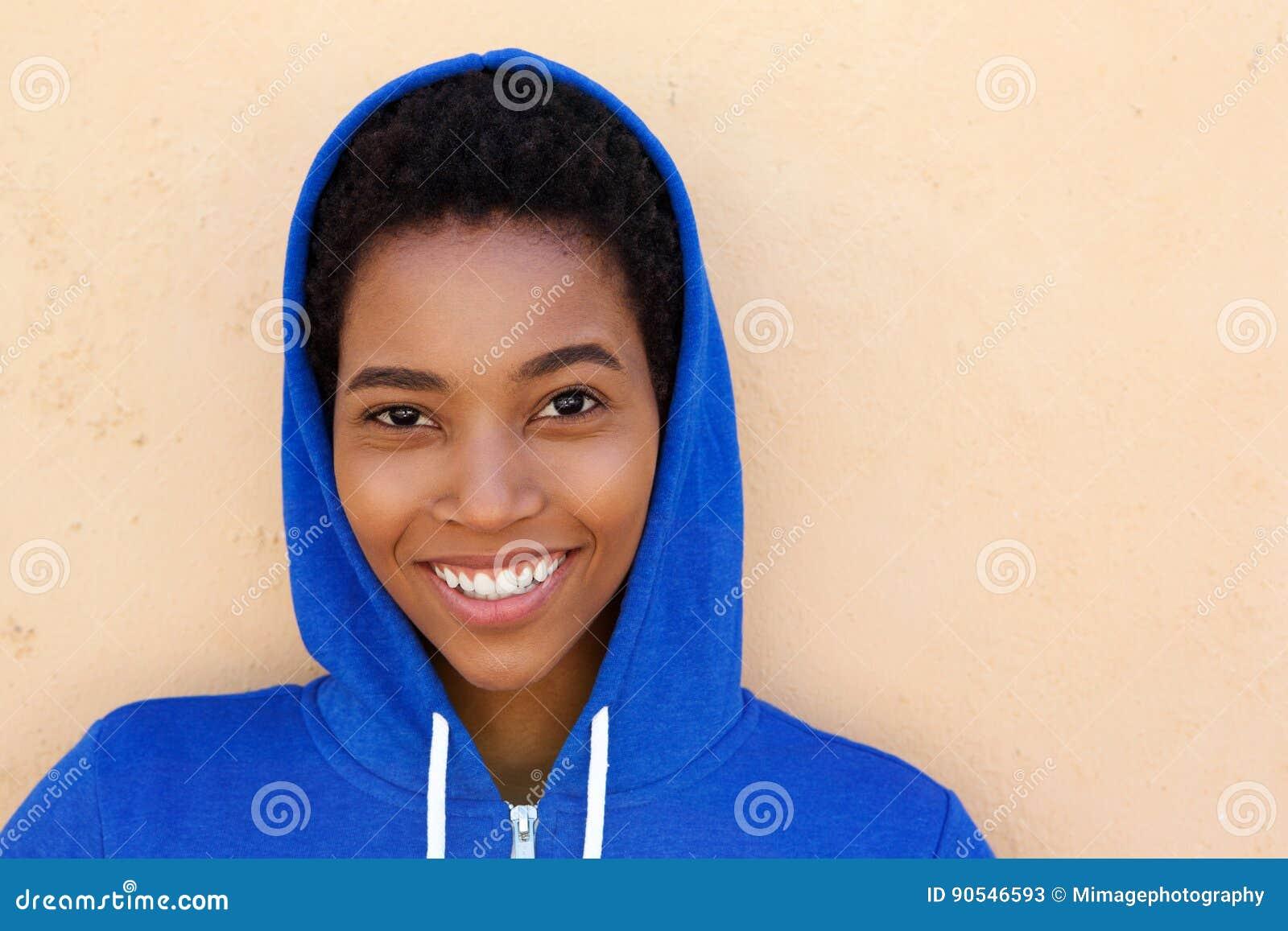 Chiuda sulla giovane donna di colore attraente con la maglia con cappuccio blu