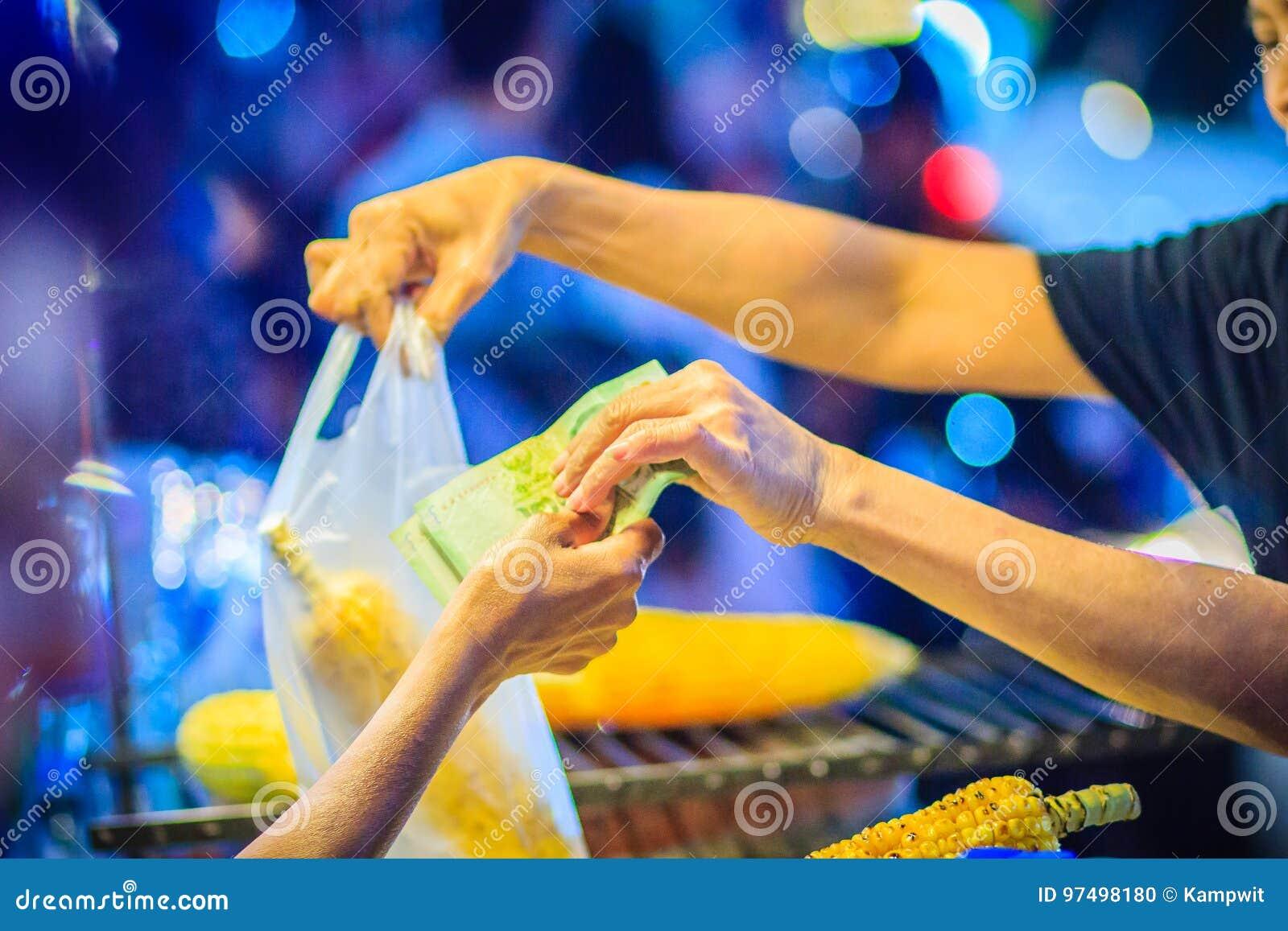 Chiuda sulla mano del venditore di alimento della via mentre grigliano e vendendo la f
